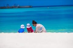 Молодая мама и маленькие девочки играя на белое песочном Стоковое фото RF
