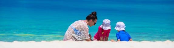 Молодая мама и маленькие девочки играя на белое песочном Стоковые Фотографии RF