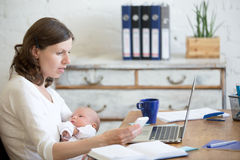 Молодая мама работая и держа ребенка в офисе Стоковые Фото
