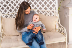 Молодая мать держа ее новорожденный ребенка Женщина и ребёнок ослабляют в белой спальне Интерьер питомника вектор jpg изображения Стоковые Фотографии RF