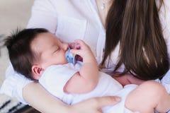 Молодая мать держа ее новорожденный ребенка стоковые изображения