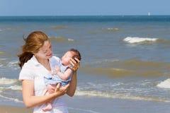 Молодая мать держа ее newborn дочь на пляже Стоковое фото RF