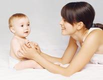 Молодая мать играя с младенцем на кровати дома стоковое изображение