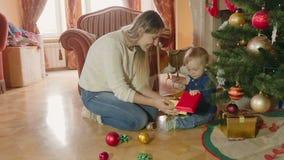 Молодая мать играя с ребёнком под рождественской елкой на живущей комнате акции видеоматериалы