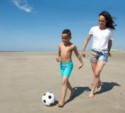 Молодая мать играя с сынком на пляже Стоковая Фотография