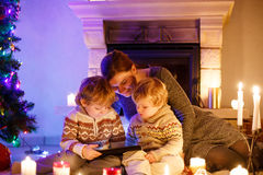 Молодая мать и его маленькие дети сидя камином на c Стоковое Изображение
