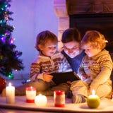 Молодая мать и его маленькие дети сидя камином на c Стоковые Фотографии RF