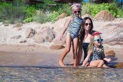 Молодая мать и 2 ее дети на экзотическом пляже дальше Стоковые Изображения