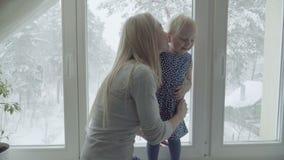 Молодая мать и ее дочь играют против окна акции видеоматериалы