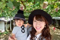 Молодая мать и ее ребенок есть виноградины Стоковые Изображения RF