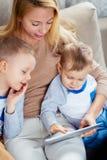 Молодая мать и к мальчикам смотря на экране таблетки Стоковые Изображения RF