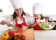 Молодая мать и маленькая дочь на кухне дома подготавливая салат для рисбермы обеда нося и шляпы кашевара Стоковое Изображение