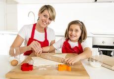 Молодая мать и маленькая сладостная дочь варя в кухне подготавливая пустыню с штангой вращающей оси Стоковые Изображения
