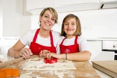 Молодая мать и маленькая сладостная дочь варя в кухне подготавливая пустыню с штангой вращающей оси Стоковое Изображение