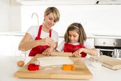 Молодая мать и маленькая сладостная дочь варя в кухне подготавливая пустыню с штангой вращающей оси Стоковое фото RF
