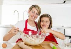 Молодая мать и маленькая сладостная дочь в рисберме кашевара варя совместно печь на современной домашней кухне Стоковые Изображения RF