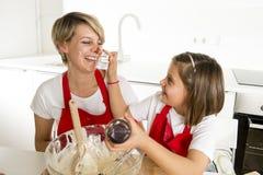 Молодая мать и маленькая сладостная дочь в рисберме кашевара варя совместно печь дома кухню Стоковые Изображения