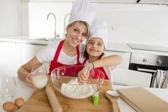 Молодая мать и маленькая сладостная дочь в шляпе кашевара и рисберма варя совместно печь дома кухню Стоковое Изображение RF