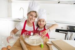 Молодая мать и маленькая сладостная дочь в шляпе кашевара и рисберма варя совместно печь дома кухню Стоковое фото RF