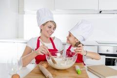 Молодая мать и маленькая сладостная дочь в шляпе кашевара и рисберма варя совместно печь дома кухню Стоковое Изображение