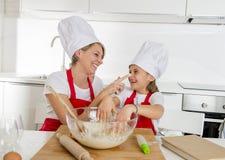 Молодая мать и маленькая сладостная дочь в шляпе кашевара и рисберма варя совместно печь дома кухню Стоковая Фотография RF
