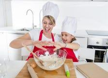 Молодая мать и маленькая сладостная дочь в шляпе кашевара и рисберма варя совместно печь дома кухню Стоковые Фотографии RF