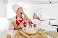 Молодая мать и маленькая сладостная дочь в шляпе кашевара и рисберма варя совместно печь дома кухню Стоковое Фото