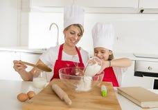 Молодая мать и маленькая сладостная дочь в шляпе кашевара и рисберма варя совместно печь дома кухню Стоковая Фотография