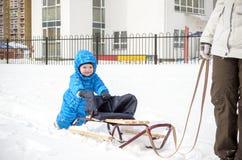 Молодая мать и мальчик наслаждаясь ездой саней Sledding ребенка Розвальни катания ребенк малыша Игра детей outdoors в снеге малыш Стоковая Фотография RF