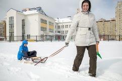 Молодая мать и мальчик наслаждаясь ездой саней Sledding ребенка Розвальни катания ребенк малыша Игра детей outdoors в снеге малыш Стоковые Фото