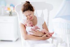 Молодая мать и newborn младенец в белой спальне Стоковые Изображения