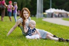 Молодая мать на коньках ролика с ее младенцем Стоковые Изображения