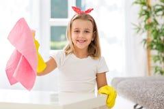 Молодая мать порции маленькой девочки стоимости к очищая дому Стоковые Изображения