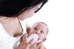 Молодая мать подавая ее изолированный младенец стоковые изображения