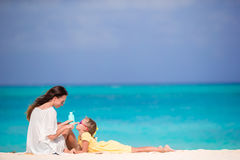 Молодая мать прикладывая сливк солнца к носу дочери на каникулах bach в горячем дне Стоковое Изображение RF