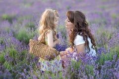 Молодая мать при молодая дочь усмехаясь на поле лаванды Дочь сидя на руках матери Девушка в красочном Стоковое Изображение