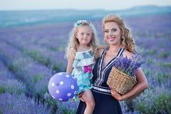 Молодая мать при молодая дочь усмехаясь на поле лаванды Дочь сидя на руках матери Девушка в красочном Стоковые Изображения RF