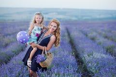 Молодая мать при молодая дочь усмехаясь на поле лаванды Дочь сидя на руках матери Девушка в красочном Стоковое Фото