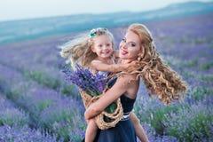 Молодая мать при молодая дочь усмехаясь на поле лаванды Дочь сидя на руках матери Девушка в красочном Стоковое фото RF