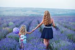 Молодая мать при молодая дочь усмехаясь на поле лаванды Дочь сидя на руках матери Девушка в красочном Стоковые Фото