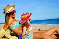 Молодая мать сидя с дочерью на пляже Стоковое Фото