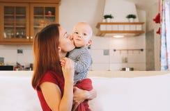 Молодая мать с ее младенцем на интерьере кресла дома Стоковое фото RF