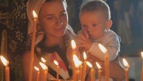 Молодая мать с маленьким сыном наблюдает свечами горения в церков сток-видео