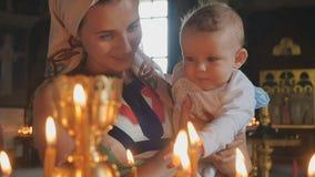 Молодая мать с младенцем наблюдает горящими свечами в церков в slowmotion акции видеоматериалы