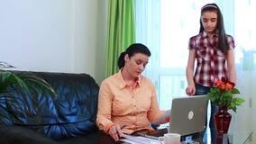 Молодая мать с портативным компьютером потревожилась о оплачивать счеты