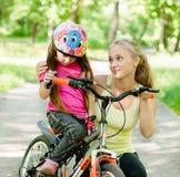 Молодая мать утихомиривает унылую дочь которая не получили, что ехала велосипед Стоковая Фотография