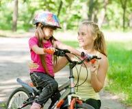 Молодая мать утихомиривает унылую дочь которая не получили, что ехала велосипед Стоковые Изображения RF