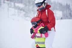 Молодая мать уча ей немногому 5 старого лет катания на лыжах doughter стоковая фотография