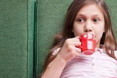 Молодая маленькая девочка выпивая от малой красной чашки стоковые фото
