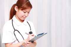 Молодая медсестра японца заполняет медицинскую диаграмму Стоковое фото RF